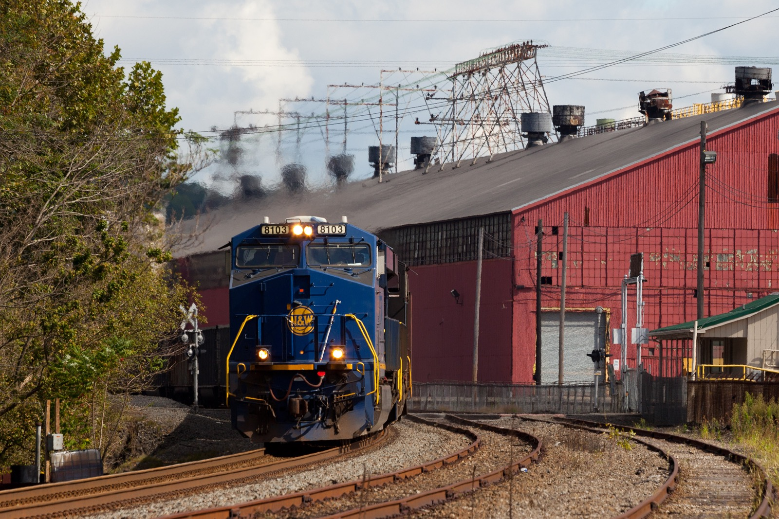 With the former Wheeling-Pittsburgh mill in the background, GE ES44AC NS 8103 painted Norfolk & Western brings the N23 Mine Job south through town. N23 will load at Bailey Mine and return the loads to Shire Oaks.