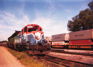 The Delaware & Hudson's engine 506 was painted in a Bicentennial commemorative scheme in 1976. Morrison-Knudsen rebuilt this RS3M locomotive in the mid-70s, creating a rather odd chopped nose. A NYSW Sea-Land stack train passes in the background. East Binghamton Yard, Conklin, N.Y. sometime in 1988.